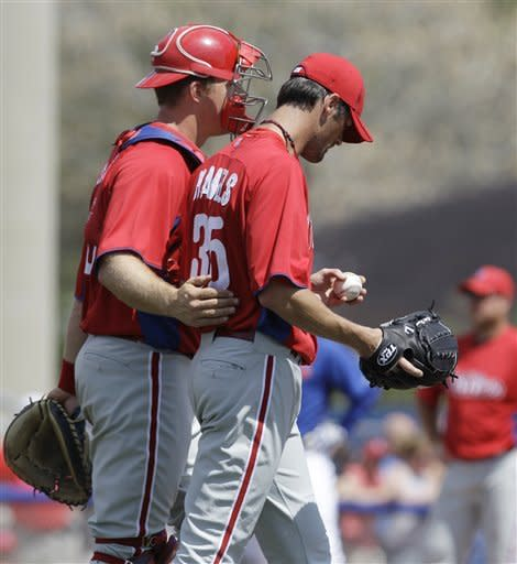 Philadelphia Phillies catcher Erik Kratz, left, accompanies starting pitcher Cole Hamels back to the mound in the fourth inning of a spring training baseball game against the Toronto Blue Jays in Dunedin, Fla., Sunday, March 18, 2012. (AP Photo/Kathy Willens)