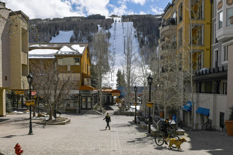 This Tuesday, March 24, 2020 photo shows people walking through empty streets at the base of Vail Ski Resort after the resort closed for the season amid the COVID-19 pandemic, in Vail, Colo. Ski resorts across the West that were shut down amid coronavirus fears are grappling with an economic blow at a time they would normally be welcoming hordes of spring break revelers.  (AP Photo/Michael Ciaglo)