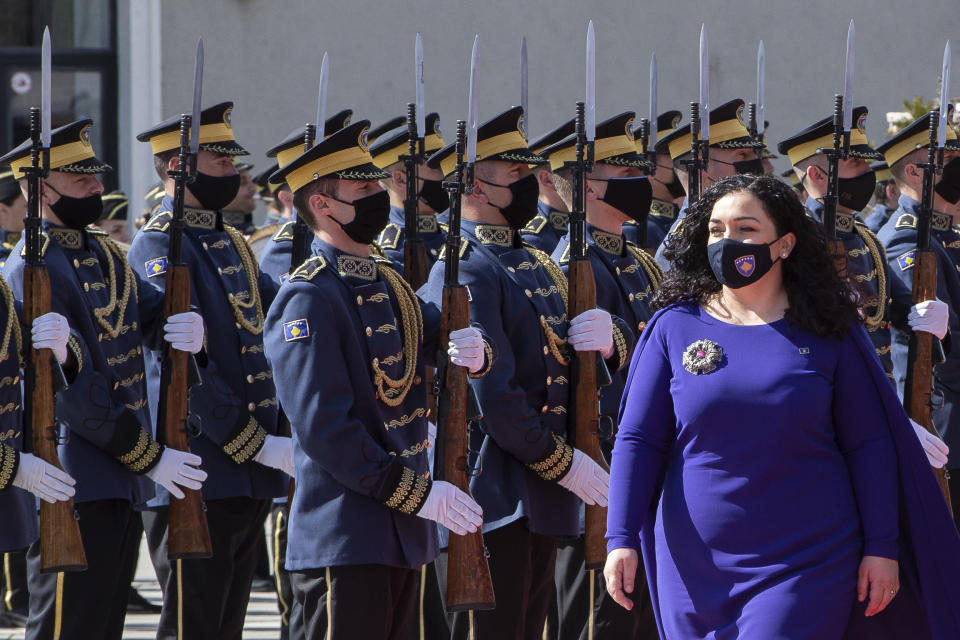 Kosovo newly elected president Vjosa Osmani-Sadriu, inspects the Guard of Honour during a presidential hand over ceremony in capital Pristina, Kosovo, on Tuesday, April 6, 2021. 38-year old Osmani took over the presidency after being elected to the post during a two-day extraordinary session of parliament.(AP Photo/ Visar Kryeziu)