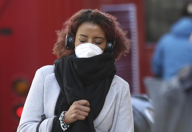 LONDON, UNITED KINGDOM - MARCH 15: People wear medical masks as a precaution against coronavirus (COVID-19) in central London, United Kingdom on March 15, 2020. In the weekend the total number of coronavirus deaths reached 35 with 1372 confirmed cases in UK. (Photo by Ilyas Tayfun Salci/Anadolu Agency via Getty Images)