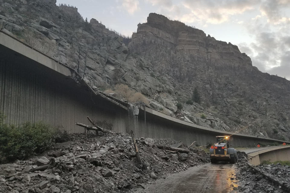 In this photo provided by the Colorado Department of Transportation, equipment works to clear mud and debris from a mudslide on Interstate-70 through Glenwood Canyon, Colo., on Friday, July 30, 2021. Authorities say more than 100 people had to spend the night on the highway, including nearly 30 who took refuge inside a highway tunnel along I-70 in Glenwood Canyon after rain over an area burned by a wildfire triggered the mudslides in Western Colorado. The people were caught with their vehicles Thursday night, July 29, 2021 and it took crews nine hours to carve out a path through the mud to reach them about 6:30 a.m. Friday, Garfield County Sheriff's Office spokesman Walt Stowe said. (Colorado Department of Transportation via AP)