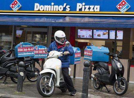 A staff member delivers take-away pizzas to customers at a Domino's Pizza store in Berlin