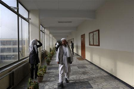 A member of the Loya Jirga, or grand council, walks at a corridor to attend a committee session in Kabul November 22, 2013. REUTERS/Omar Sobhani