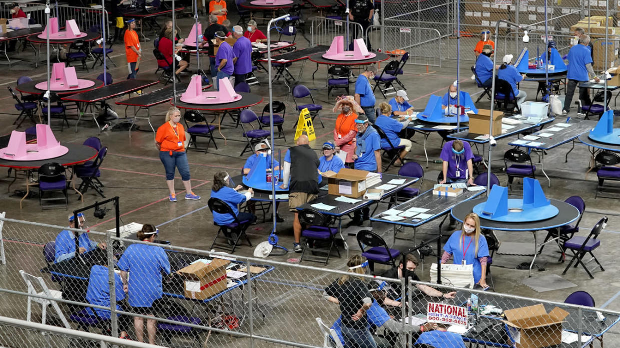 In this May 6, 2021 file photo, Maricopa County ballots cast in the 2020 general election are examined and recounted by contractors working for Florida-based company, Cyber Ninjas at Veterans Memorial Coliseum in Phoenix.  (Matt York/AP Photo)