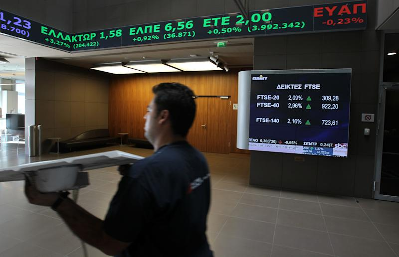 """A technician passes next to charts of the Stock Exchange in Athens Tuesday, Oct. 30, 2012. Shares recovered slightly from heavy losses Monday, amid continued uncertainty over a new austerity package due to divisions in the country's coalition government. Conservative Prime Minister Antonis Samaras said Tuesday that the government had essentially ended negotiations on new austerity measures and warned of """"chaos"""" if the reforms are not passed. (AP Photo/Thanassis Stavrakis)"""