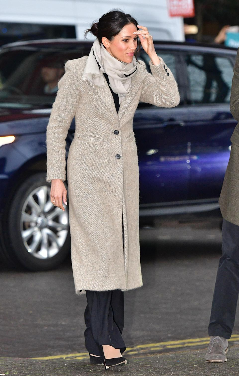 """<p>On 9 January 2018, Meghan Markle and Prince Harry visited a Brixton radio station to mark their second royal engagement together. For the momentous occasion, Markle recycled her go-to Smythe coat and teamed the look with Burberry trousers, a Jigsaw scarf and Marks and Spencer's <a rel=""""nofollow noopener"""" href=""""http://www.marksandspencer.com/wool-blend-round-neck-bell-sleeve-jumper/p/p22511692?OmnitureRedirect=Wool+Blend+Round+Neck+Bell+Sleeve+Jumper+"""" target=""""_blank"""" data-ylk=""""slk:knit"""" class=""""link rapid-noclick-resp"""">knit</a>. <em>[Photo: Getty]</em> </p>"""