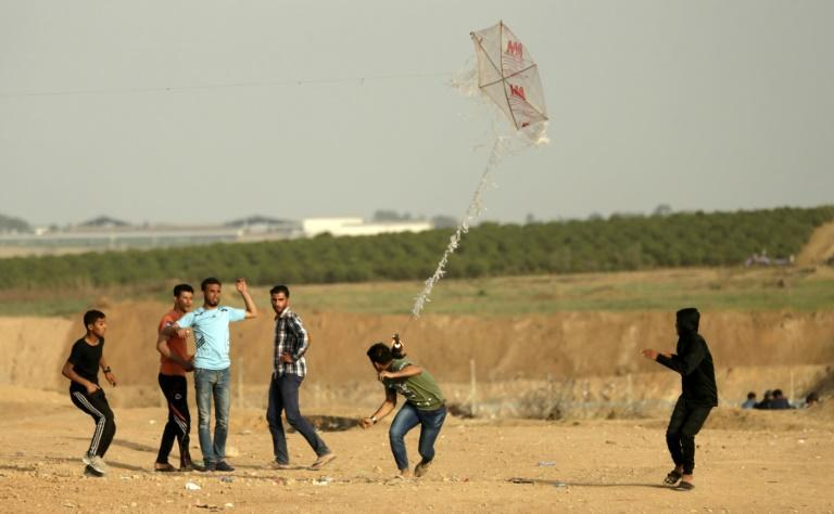 Palestinian youths try to fly a kite carrying a Molotov cocktail over the Gaza-Israel border on April 18, 2018