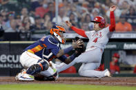 Houston Astros catcher Martin Maldonado, left, tries to make the tag against Los Angeles Angels' Jose Iglesias (4) as he safely slides into home plate during the fifth inning of a baseball game Sunday, April 25, 2021, in Houston. (AP Photo/Michael Wyke)