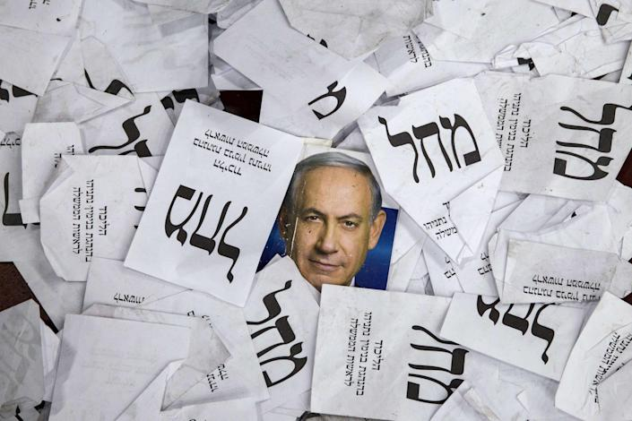 Copies of ballots papers and campaign posters for Israel's Prime Minister Benjamin Netanyahu's Likud Party lie on the ground in the aftermath of the country's parliamentary elections, early on March 18, 2015 in Tel Aviv. On Sunday,  Israel's parliament is poised to cast a historic vote that could end Benjamin Netanyahu's 12-year tenure as prime minister.