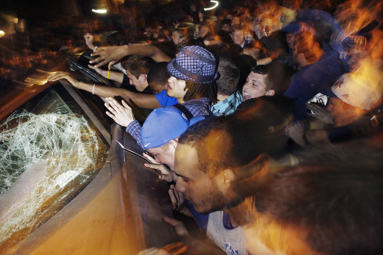 In this Saturday, March 31, 2012, photo, Kentucky fans overturn a car as they celebrate Kentucky's 69-61 win over Louisville in an NCAA Final Four semifinal college basketball tournament game in Lexington, Ky. Lexington police say they are prepared to control crowds near the University of Kentucky's Lexington campus when Kentucky plays Kansas in the national championship basketball game on Monday. (AP Photo/Christian Randolph)