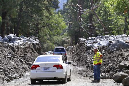 Vehicles pass through an area damaged by a mudflow triggered by flash floods in the San Bernardino National Forest community of Forest Falls, California August 4, 2014. REUTERS/Jonathan Alcorn