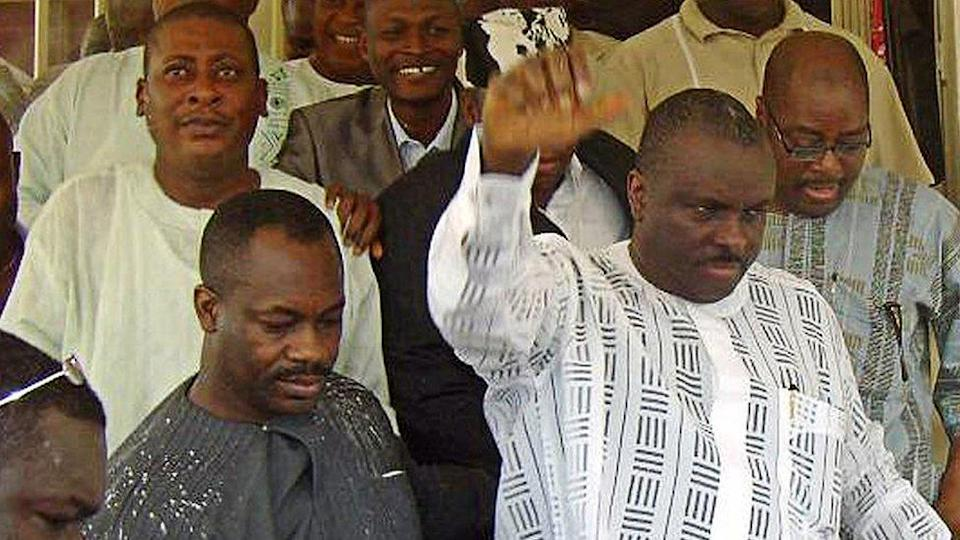Former governor of oil-rich Delta State James Ibori (R) raises his hand to acknowledge his supporters after leaving the courtroom at an Asaba High Court on December 17, 2009