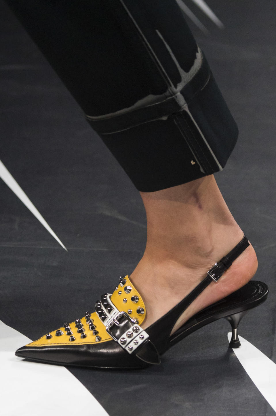 <p><i>Yellow and black slingback studded heels from the SS18 Prada collection. (Photo: ImaxTree) </i></p>
