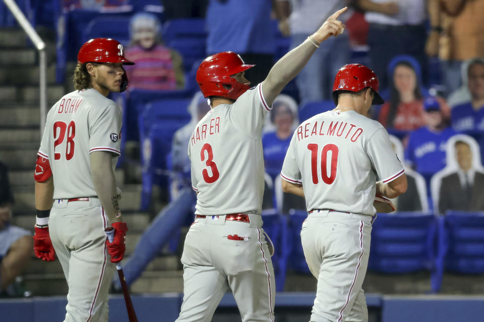 Philadelphia Phillies' Bryce Harper (3) gestures to Rhys Hoskins (not shown) whose double scored three runs as Alec Bohm (28) and J.T. Realmuto react during the seventh inning of a baseball game against the Toronto Blue Jays, Friday, May 14, 2021, in Dunedin, Fla. (AP Photo/Mike Carlson)