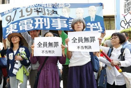 """Women hold banners reading """"Everyone is not guilty, unjust sentence"""" in front of Tokyo District Court in Tokyo"""