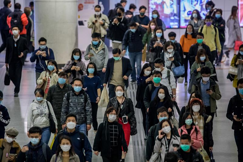 Hong Kong commuters wear masks as the cases of the virus outside of China continue to rise.