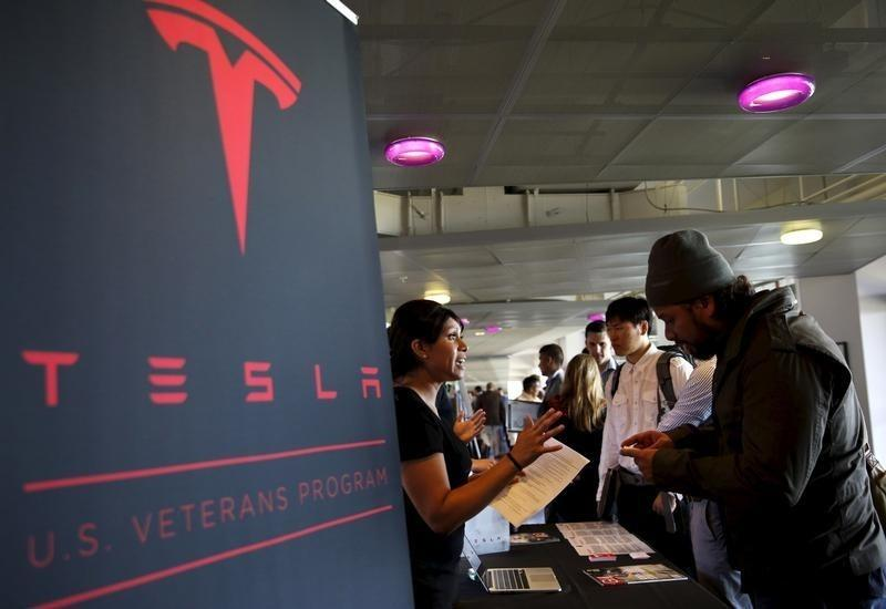 A recruiter from Tesla talks with a job seeker at a military job fair in San Francisco