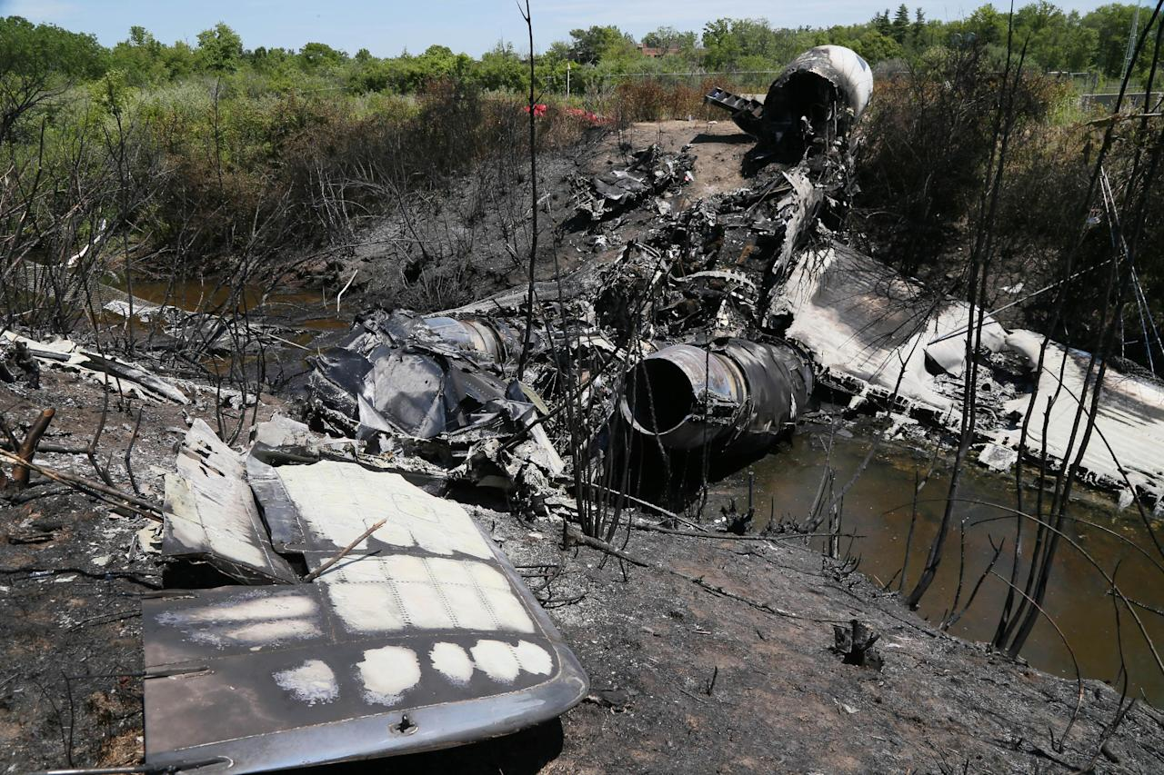 Wreckage lies at the scene Monday, June 2, 2014, in Bedford, Mass., where a plane plunged down an embankment and erupted in flames during a takeoff attempt at Hanscom Field Saturday night. Lewis Katz, co-owner of the Philadelphia Inquirer, and six other people died in the crash. (AP Photo/Boston Herald, Mark Garfinkel, Pool)
