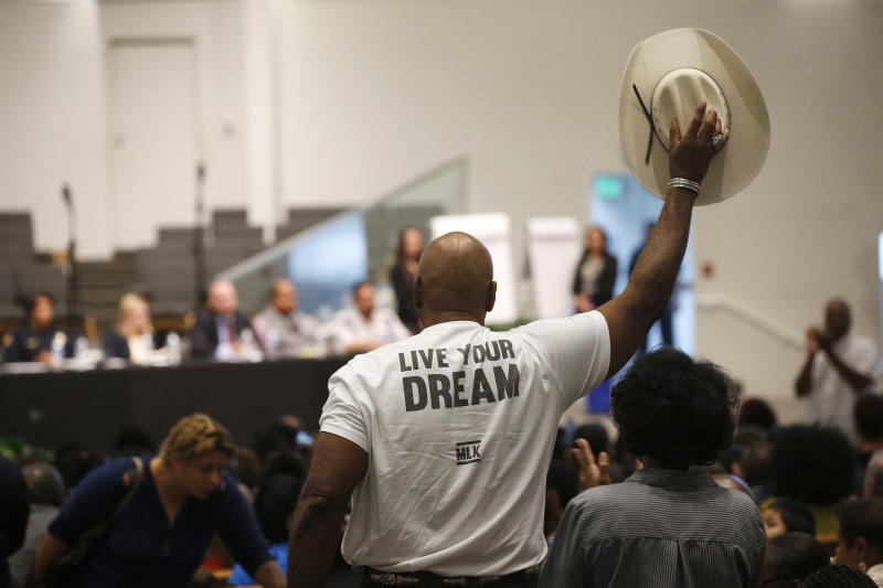 A Phoenix resident stands up to wave his cowboy hat in support of a speaker at a community meeting, Tuesday, June 18, 2019, in Phoenix. The community meeting stems from reaction to a videotaped encounter that surfaced recently of Dravon Ames and his pregnant fiancee, Iesha Harper, having had guns aimed at them by Phoenix police during a response to a shoplifting report, as well as the issue of recent police-involved shootings in the community. (AP Photo/Ross D. Franklin)