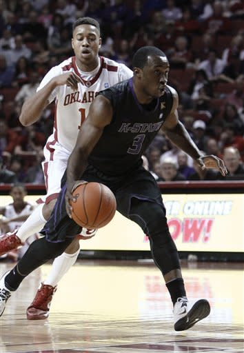 Kansas State guard Martavious Irving (3) drives to the basket in front of Oklahoma Isaiah Cousins (11) during the first half of an NCAA college basketball game in Norman, Okla., Saturday, Feb. 2, 2013. (AP Photo/Alonzo Adams)