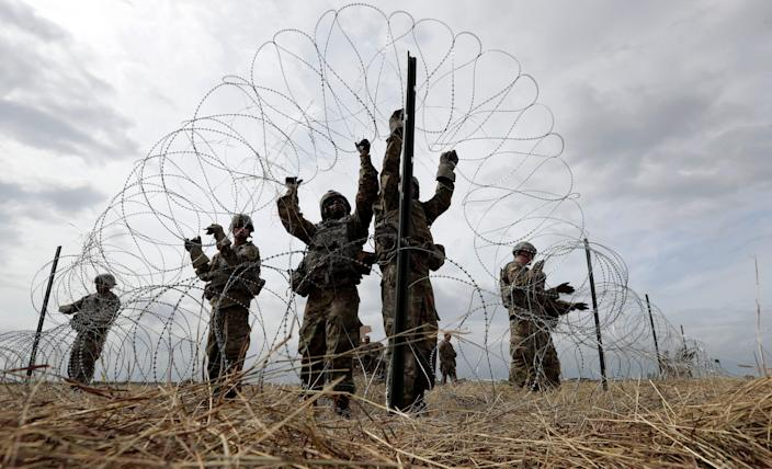Members of a U.S Army engineering brigade place Concertina wire around an encampment for troops, Department of Defense and U.S. Customs and Border Protection near the U.S.-Mexico International bridge, Sunday, Nov. 4, 2018, in Donna, Texas. (AP Photo/Eric Gay)