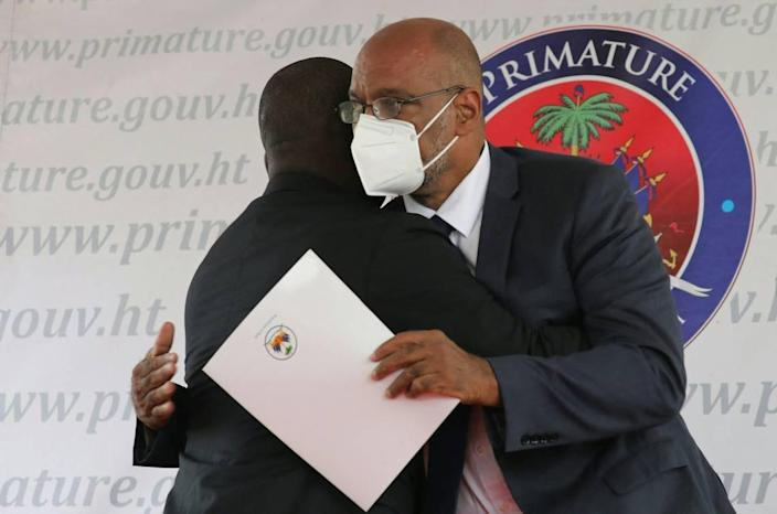 Interim Prime Minister Claude Joseph, left, hugs designated Prime Minister Ariel Henry during a ceremony at La Primature in Port-au-Prince, Haiti, on July 20, 2021. The ceremony comes as designated Prime Minister Ariel Henry prepared to replace interim Prime Minister Claude Joseph after the July 7 attack at the president's private home.