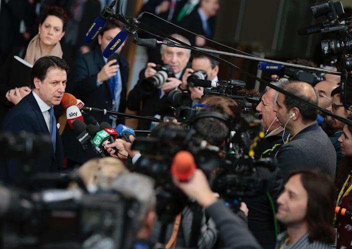 Italian Prime Minister Giuseppe Conte speaks with the media as he arrives for an EU summit at the European Council building in Brussels, Friday, Feb. 21, 2020.
