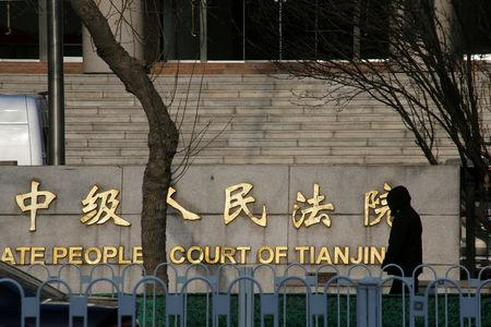 FILE PHOTO: Man walks outside an Intermediate People's Court where prominent rights lawyer Wang Quanzhang is being tried, in Tianjin
