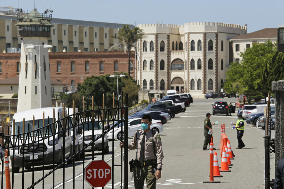 "FILE - In this July 9, 2020 file photo, a correctional officer closes the main gate at San Quentin State Prison in San Quentin, Calif. A California appeals court has ordered state corrections officials to cut the population of one of the world's most famous prisons to less than half of its designed capacity, citing officials' ""deliberate indifference"" to the plight of inmates during the coronavirus pandemic. State prison officials said Wednesday, Oct. 21, 2020, that they are deciding whether to appeal the order, which otherwise will force them to parole or transfer about 1,100 inmates serving time in San Quentin State Prison north of San Francisco. (AP Photo/Eric Risberg, File)"