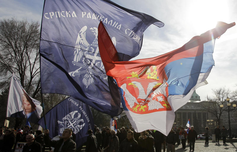 Protesters wave Serbian flag, right and Radical party flags during the protest in front of the presidency building in Belgrade, Serbia, Tuesday, Feb. 5, 2013. Dozens of ultra-nationalists have accused Serbia's president of treason for agreeing to meet with his counterpart from Kosovo for the first time since the end of the war in 1999. The talks between Tomislav Nikolic and Atifete Jahjaga on Wednesday in Brussels, Belgium, will be part of an EU-brokered effort to improve ties between the former foes. (AP Photo/Darko Vojinovic)