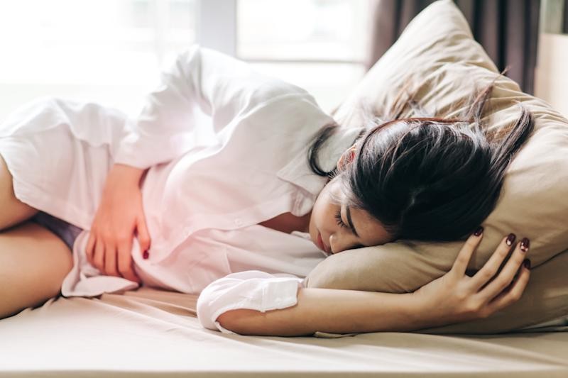 Woman Touching Abdomen In Pain While Sleeping On Bed At Home