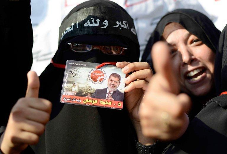 Female supporters of Egyptian President Mohamed Morsi hold up his image during a rally outside Cairo University on June 2, 2013. Morsi told Egyptians that he had been freely elected little more than a year ago and intended to continue to carry out his duties despite mass protests demanding his resignation