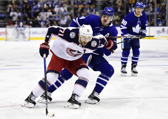 Columbus Blue Jackets left wing Nick Foligno (71) protects the puck from Toronto Maple Leafs center Auston Matthews (34) during first-period NHL hockey game action in Toronto, Monday, Oct. 21, 2019. (Frank Gunn/The Canadian Press via AP)