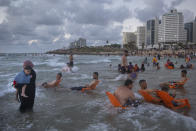 Palestinians enjoy the day on the beach during the Eid Al Adha festival in Tel Aviv, Israel, Wednesday, July 21, 2021. The major Muslim holiday, at the end of the hajj pilgrimage to Mecca, is observed around the world by believers and commemorates prophet Abraham's pledge to sacrifice his son as an act of obedience to God. (AP Photo/Oded Balilty)