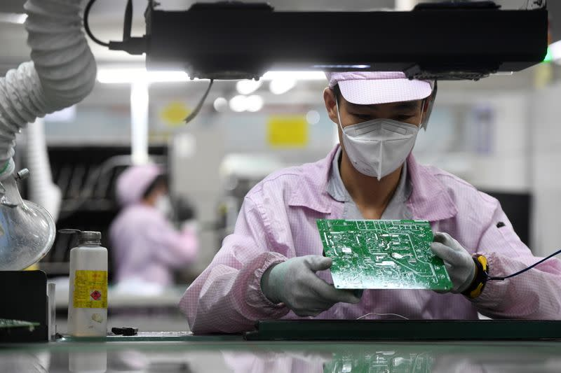 Employee inspects a circuit board at a Gree factory in Wuhan