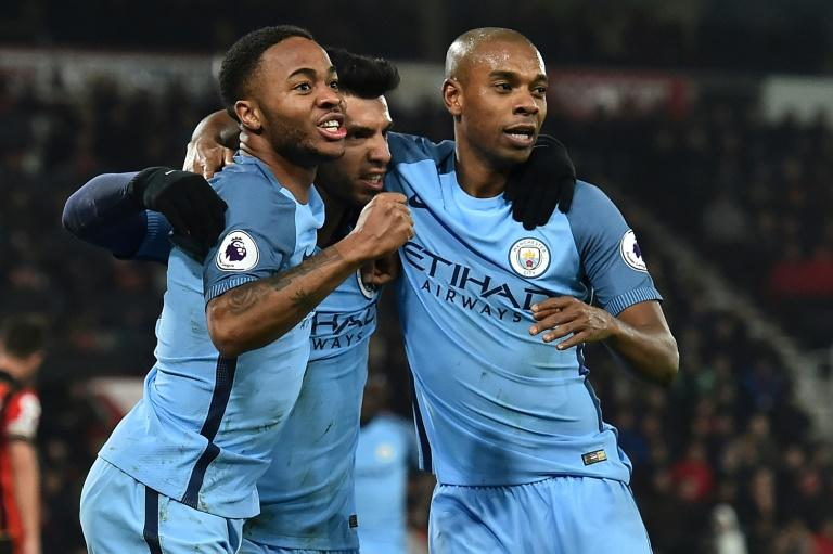 Manchester City's Sergio Aguero (C) celebrates with teammates Raheem Sterling (L) and Fernandinho after scoring a goal during their English Premier League match against Bournemouth, at the Vitality Stadium in Bournemouth, on February 13, 2017