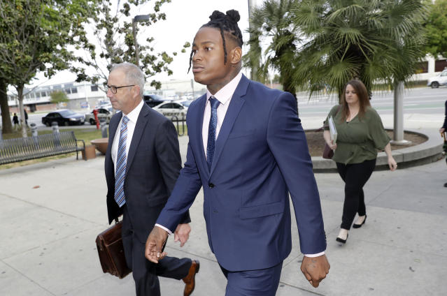 San Francisco 49ers linebacker Reuben Foster, center, arrives with his attorney Joshua Bentley, left, at Santa Clara County Superior Court, Thursday, May 17, 2018, in San Jose, Calif. Foster pleaded not guilty Tuesday, May 8, 2018, to charges stemming from allegations that he attacked his then-girlfriend in their home in February. A preliminary hearing has been scheduled today, at which point Foster's former girlfriend, Elissa Ennis, may testify under oath. (AP Photo/Marcio Jose Sanchez)