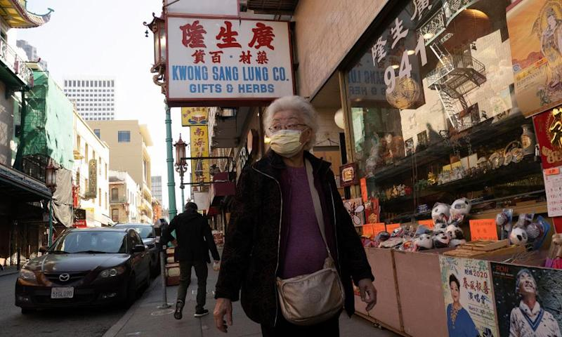 A woman walks through Chinatown while wearing a protective mask on Wednesday.