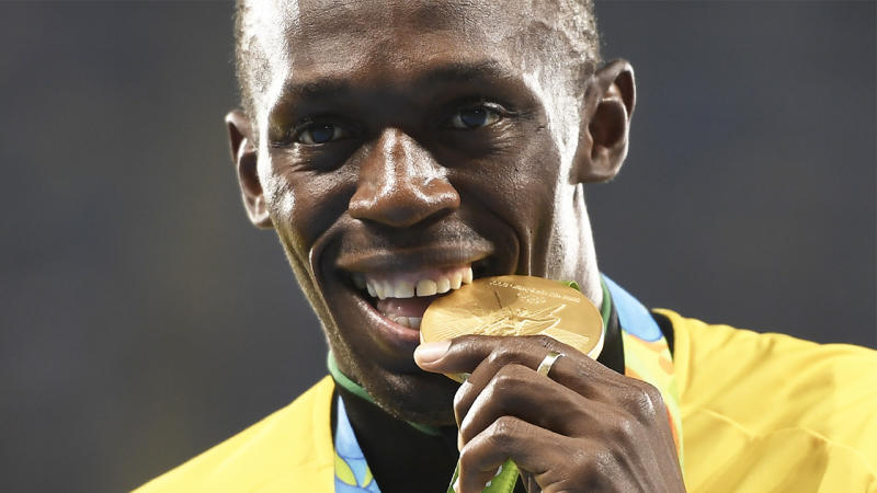 Usain Bolt biting the gold medal after he won the race.