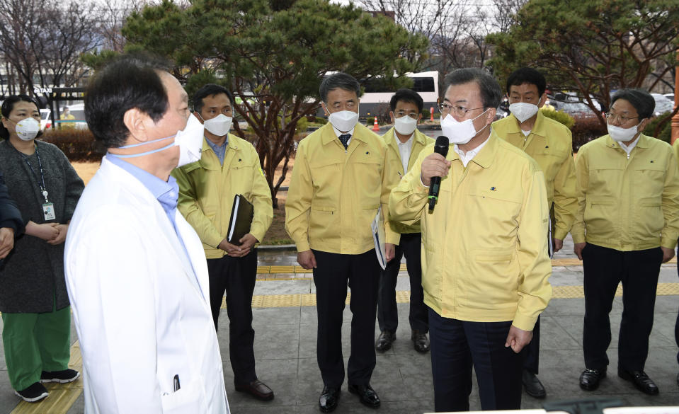 South Korean President Moon Jae-in, front right, talks to a president of Daegu Medical Center, You Wansik, at the Daegu Medical Center in Daegu, South Korea, Tuesday, Feb. 25, 2020. China and South Korea on Tuesday reported more cases of a new viral illness that has been concentrated in North Asia but is causing global worry as clusters grow in the Middle East and Europe. (Bae Hun-shik/Newsis via AP)
