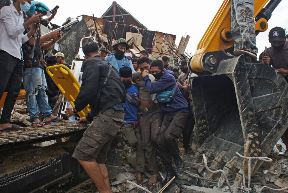 Rescuers assist a survivor pulled out from the ruin of a government building collapsed during an earthquake in Mamuju, West Sulawesi, Indonesia, Friday, Jan. 15, 2021. A strong, shallow earthquake shook Indonesia's Sulawesi island just after midnight Friday, toppling homes and buildings, triggering landslides and killing a number of people. (AP Photo/Azhari Surahman)