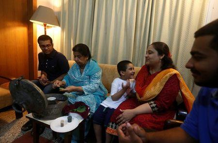 Rehana Khursheed Hashmi, 75 (2nd L) migrated from India with her family in 1960 and whose relatives, live in India, prepares pan (beetle leaf) while sitting with her grandsons and daughter in-law at her residence in Karachi, Pakistan August 7, 2017. REUTERS/Akhtar Soomro