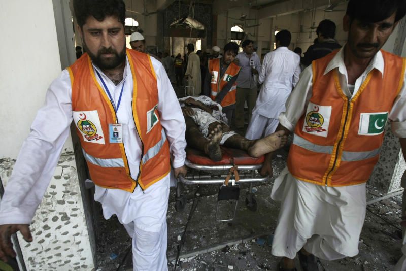 Pakistani volunteers carry a dead body following a suicide bombing at a Shiite mosque in Peshawar, Pakistan on Friday, June 21, 2013. Militants opened fire on a Shiite Muslim mosque where worshippers were gathering for Friday prayers, and then a suicide bomber detonated his explosives inside, killing more than a dozen people in the latest attack aimed at the minority sect, police said. (AP Photo/Mohammad Sajjad)