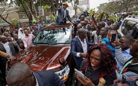 Opposition leader Raila Odinga smiles and waves to a crowd of his supporters as he leaves the Supreme Court in downtown Nairobi - Credit: Ben Curtis/AP