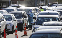 Cars queue at a COVID-19 test centre in Auckland, New Zealand, Thursday, Aug. 13, 2020. Health authorities in New Zealand are scrambling to trace the source of a new outbreak of the coronavirus as the nation's largest city goes back into lockdown. (AP Photo/Dean Purcel)