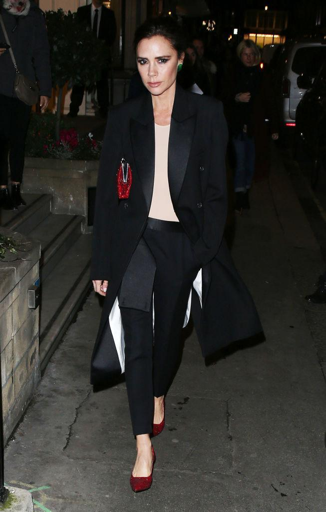 <p>Victoria Beckham dresses for the season in the perfect polished Posh Spice ensemble, brightened up with a pair of red shoes. (Photo: Neil Mockford/GC Images) </p>