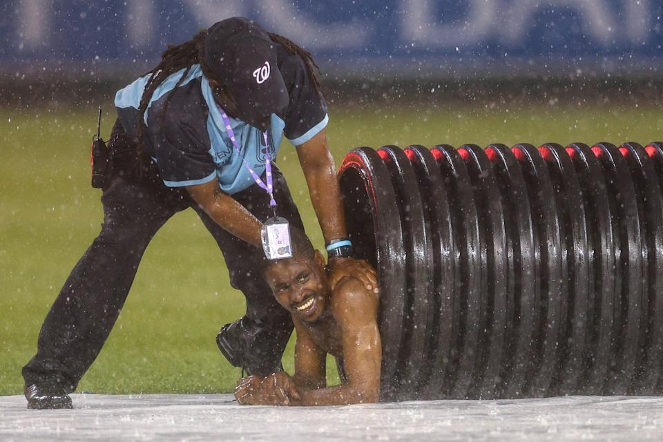 A streaker is pulled from the infield tarp roller by security during a rain delay between the Reds and Nationals at Nationals Park.