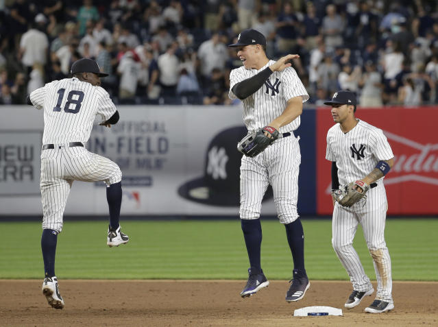 New York Yankees' Didi Gregorius (18), left, Aaron Judge, center, and Gleyber Torres celebrate after a baseball game against the Seattle Mariners at Yankee Stadium Tuesday, June 19, 2018, in New York. The Yankees defeated the Mariners 7-2. (AP Photo/Seth Wenig)