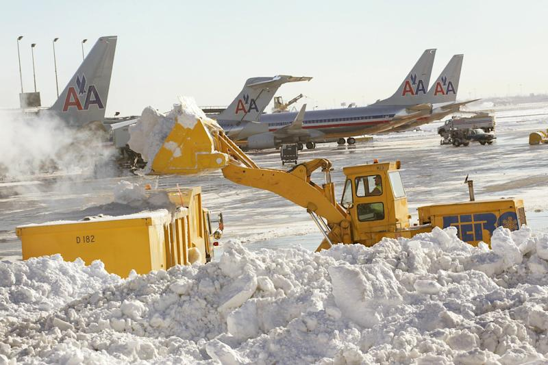 Planes on a snow-filled runway in the Midwest after a blizzard.