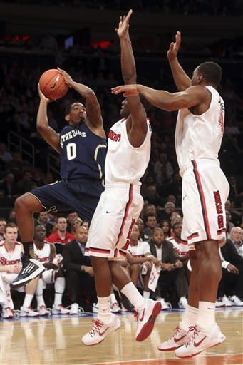 Notre Dame's Eric Atkins, left, goes up against St. John's Phil Greene IV, center, and Christian Jones during an first half of the NCAA college basketball game, Tuesday, Jan. 15, 2013, at Madison Square Garden in New York